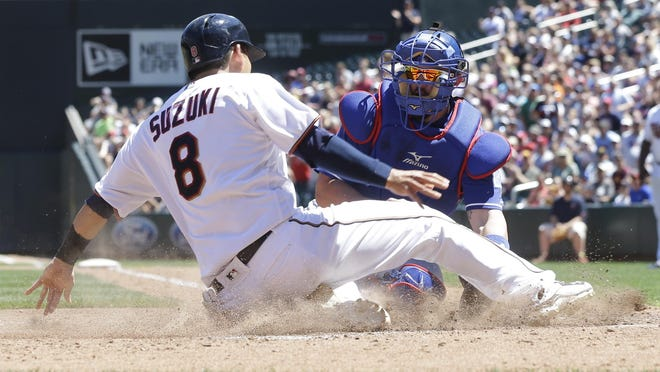 Minnesota Twins' Kurt Suzuki, right, is tagged out by Texas Rangers catcher Bobby Wilson as he is tagged out at the plate trying to score on a Eddie Rosario double in the fourth inning of a baseball game Sunday, July 3, 2016, in Minneapolis. (AP Photo/Jim Mone)