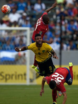 Costa Rica defender Roy Miller and Jamaica forward Giles Barnes and Costa Rica midfielder Jose Miguel Cubero battle for the ball during the second half of CONCACAF Gold Cup group play at Stub Hub Center.