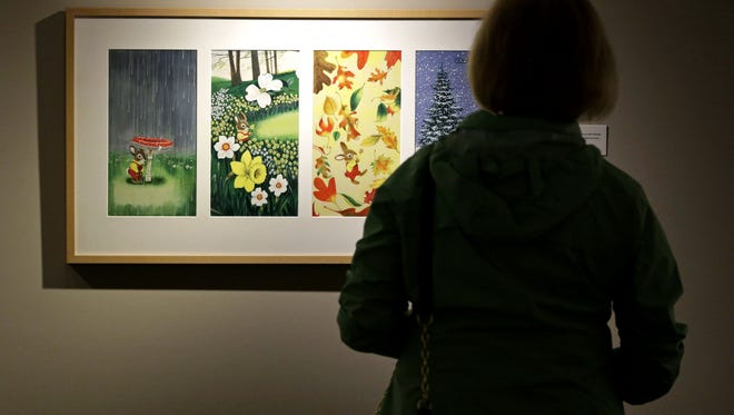 Jan DeMenter of Menasha reads details on a display Saturday at the Trout Museum of Art. The new exhibit features original art from Golden Books.