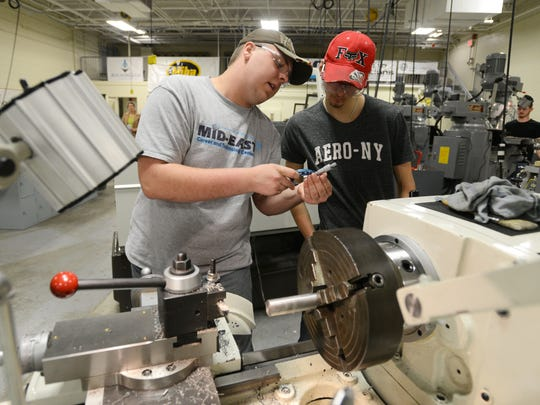 Ron Larrick, left, talks with Joey Soller in front of a CNC lathe at Mid-East Career and Technology Center's Zanesville campus.
