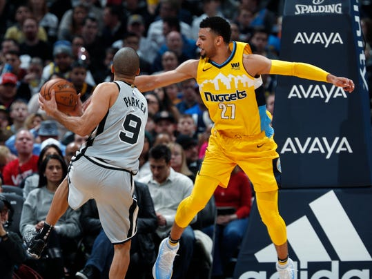 Denver Nuggets guard Jamal Murray, right, defends as San Antonio Spurs guard Tony Parker drives to the basket during the first half of an NBA basketball game Friday, Feb. 23, 2018, in Denver. (AP Photo/David Zalubowski)