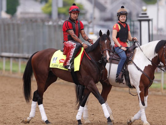 Classic Empire (left) walks on the track during morning