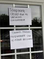 """A """"temporarily closed"""" sign is stuck to the front entrance"""