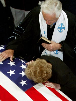 Nancy Reagan leans down to kiss the casket of her husband, President Ronald Reagan, after a private service with her family and the Rev. Wenning, left, before the public viewing period began at the Ronald Reagan Presidential Library on June 7, 2004, in Simi Valley, Calif.