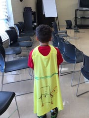 Students shows off the cape he made for the 37th Annual