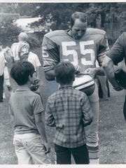 Detroit Lions linebacker/kicker Wayne Walker autographs for young fans at picture day.
