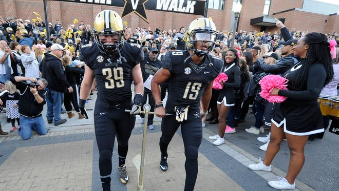 Vanderbilt fullback Bailey McElwain (39) and wide receiver C.J. Duncan (19) carry the anchor past the fans during the Star Walk before their game against Tennessee State  Saturday, Oct. 22, 2016, in Nashville, Tenn.