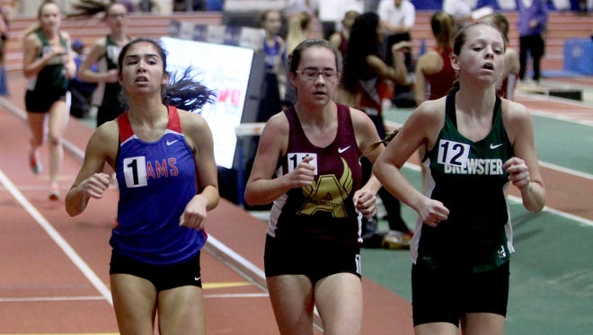 Jade Sessions of Carmel, left, laps slower runners as she wins the girls 1500 meter race at the Northern Counties Indoor Track and Field Championships at the New Balance Armory in Manhattan Jan. 28, 2017.