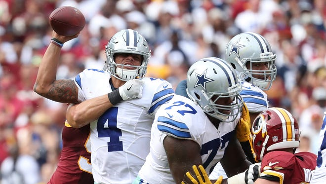Dallas Cowboys quarterback Dak Prescott (4) throws the ball while being tackled by Washington Redskins linebacker Ryan Kerrigan (91) in the fourth quarter at FedEx Field. The Cowboys won 27-23.