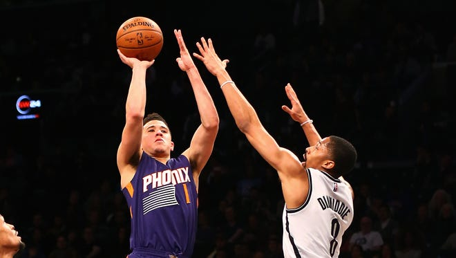 Phoenix Suns guard Devin Booker shoots the ball while being defended by Brooklyn Nets guard Spencer Dinwiddie on March 23, 2017.