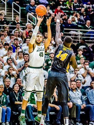 Denzel Valentine ,45, of MSU lines up a successful 3-point shot over Peter Jok of Iowa to begin scoring during their game Thursday.  Valentine would contribute 14 points while Jok would game high score with 23.