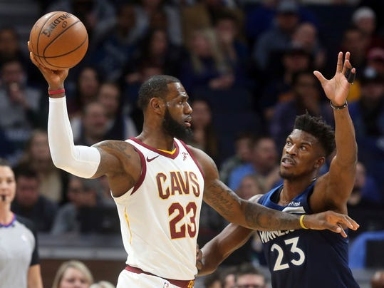 Cleveland Cavaliers' LeBron James,front left, looks to pass as Minnesota Timberwolves' Jimmy Butler defends in the first half of an NBA basketball game Monday, Jan. 8, 2018, in Minneapolis. (AP Photo/Jim Mone)
