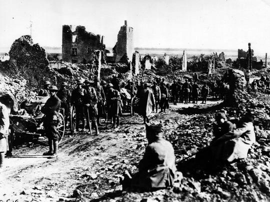 Men of the 18th Infantry, First Division, pause briefly during a march through the ruins of a French town near St. Mihiel.