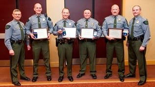 Flanked by DNR Law Enforcement Division Assistant Chief Dean Molnar at far left are Lifesaving Award honorees are, left to right, Officer Michael Drexler, Sgt. Michael Feagan, Sgt. Todd Szyska and Sgt. Ron Kimmerly. DNR Law Enforcement Chief Gary Hagler is at far right.