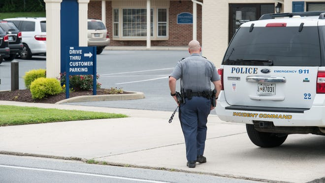 Police officers investigate the scene of a July 2015 robbery of the Hebron Savings Bank branch on Riverside Drive in Salisbury.