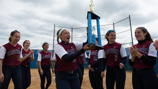 Eastern's Sara Waro, center, carries the team's first place trophy after defeating Bishop Eustace 5-3 at the 35th annual Hammonton Invitational softball tournament Saturday, April 30 in Hammonton.