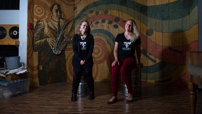 Human Village Brewing Company's Emily Barnes (left) and Megan Myers sit on kegs inside the tasting room of the Pitman brewery. The owners are committed to the venue's former life as a concert hall.