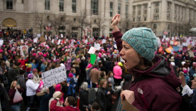 A woman rallies fellow protestors as thousands of marchers walk down Pennsylvania Ave in protest of newly elected president Donald J. Trump Saturday, Jan. 21 in Washington, D.C.