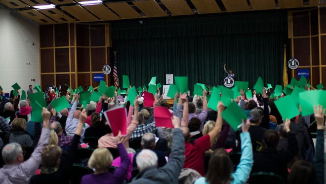 Constituents raise green cards to signify 'yes' when asked if they represent district 3 as a citizens' town hall is held in absence of congressman Tom MacArthur (R-NJ 3rd District) Wednesday night, Feb. 22 at Frances DeMasi Middle School in Marlton. The event was scheduled by local constituents and advocacy groups after repeated requests for Congressman MacArthur to hold an in person Town Hall were denied.