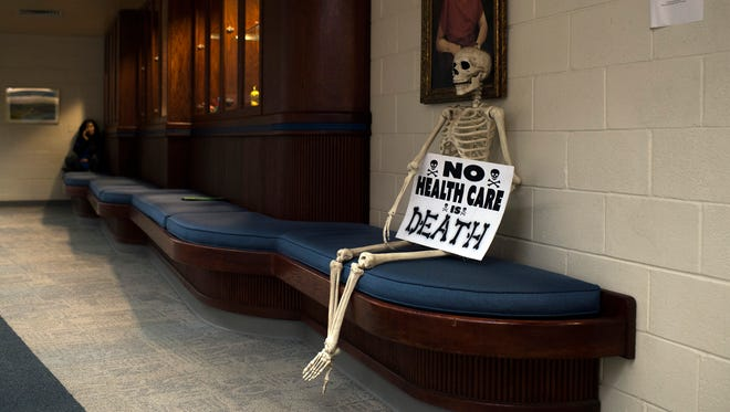 A prop skeleton is seen with a sign reading 'No Health Care is Death' in the hallway outside a citizens town hall held in absence of congressman Tom MacArthur (R-NJ 3rd District) Wednesday, Feb. 22 in Marlton.