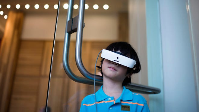 Jon Paul Corman, 9, who is legally blind, looks out a window at Philadelphia through his new eSight glasses Thursday.