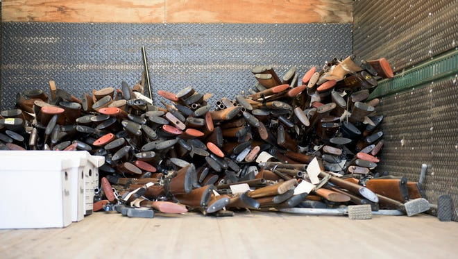 Over 600 guns are piled into a truck midway through a gun buyback program Friday, July 28, 2017 in Camden.