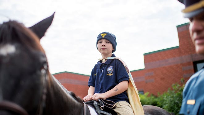 Tyler Carach, 9, known as 'Donut Boy,' rides Jake, a Morgan horse, outside the New Jersey State Police headquarters Thursday in Buena Vista.