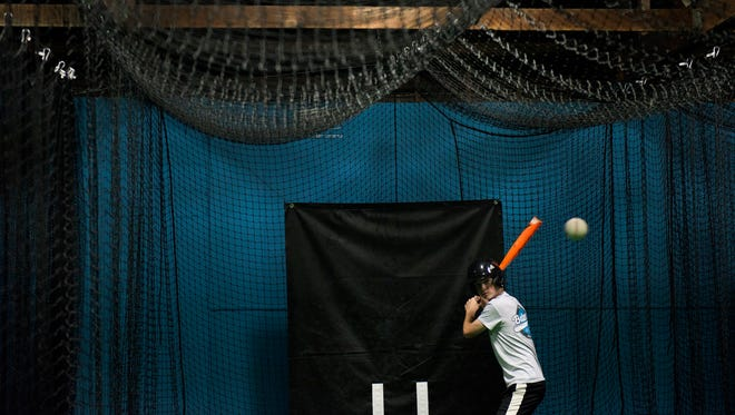 Sean Ahrens, 14, eyes a pitch from his father and co-owner David Ahrens at Batter's Alley Wednesday, Aug. 30, 2017 in Palmyra.