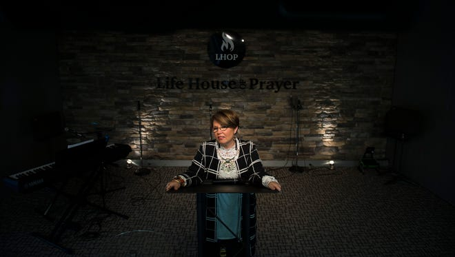 Pastor Marie Campbell stands at the pulpit at Life Church in Williamstown. Campbell leads an outreach ministry for people seeking recovery from addiction. She is herself in decades-long recovery from an IV heroin addiction, and attributes her sobriety to her faith.