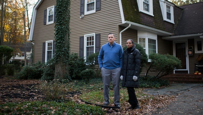 Eric Satterthwaite, left, and Danielle Satterthwaite pose in front of their home Tuesday, Nov. 14, 2017 in Cherry Hill.