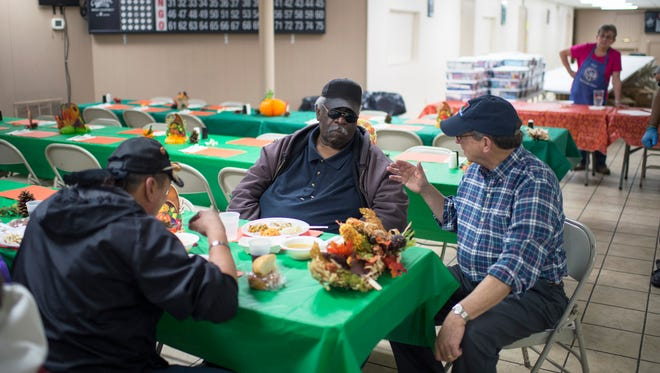 New Jersey Secretary of Agriculture Douglas H. Fisher, right, speaks with local resident Leslie Pitts during a Thanksgiving lunch Wednesday, Nov. 22, 2017 at Society of St. Vincent de Paul in Bridgeton.