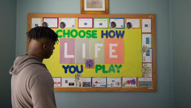 Intern Xzavier Williams, 22, looks over a career board inside Hopeworks 'N Camden Friday, Dec. 1, 2017 in Camden. Hopeworks trains city youth for careers in technology and coding while addressing issues such as trauma, family dysfunction and poverty.