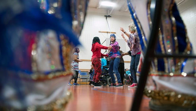 Students dance as mummers perform at the Burlington County Special Services School gym Friday, Dec. 1, 2017 in Westampton, New Jersey.
