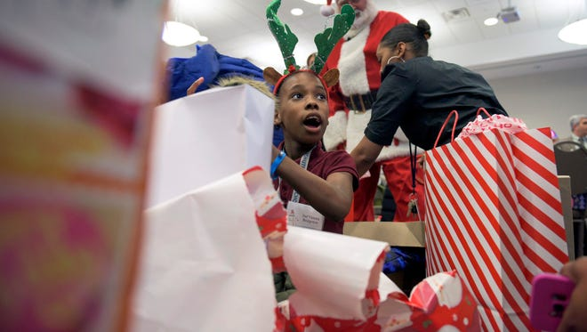Dai'Vionna Hadley, 9, of Bridgeton reacts as she gets a new jacket Wednesday, Dec. 13, 2017 at Cumberland County College in Vineland, New Jersey.