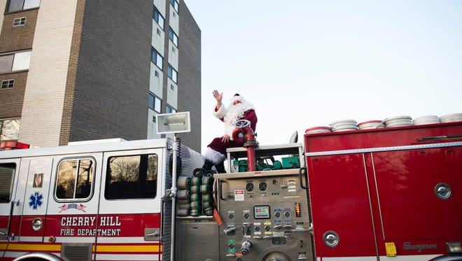Santa, portrayed by retired firefighter Alfred DiTore, arrives on a firetruck to bring gifts for the Huff-Myers family in Cherry Hill.