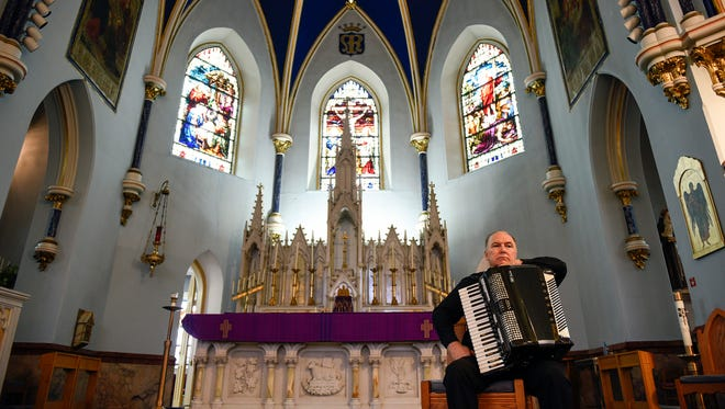Monsignor William Hodge sits with his accordion after playing inside St. Mary's Church in Gloucester City.