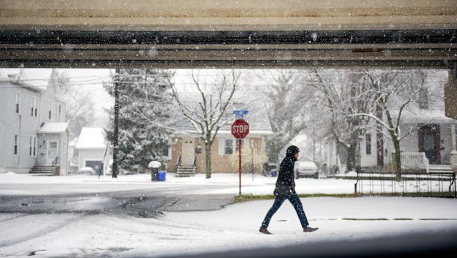 A man walks by the PATCO line as a nor'easter brings snowfall Wednesday, March 21, 2018 in Collingswood, N.J.