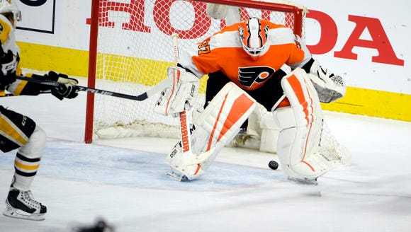 Flyers' Brian Elliott (37) watches the puck go between