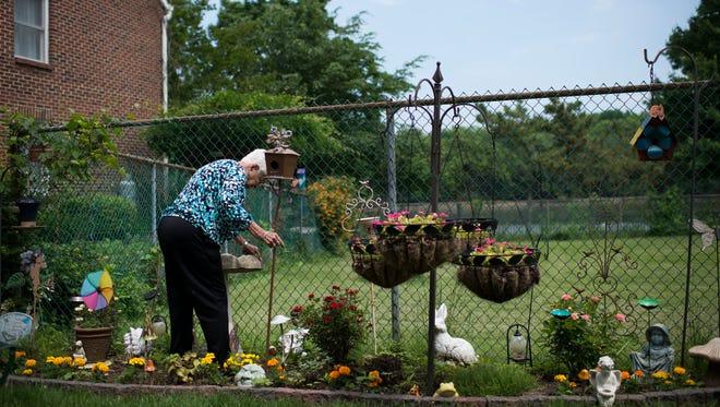 Luz Maria Hernandez de Fernandez-Andueza, 100, tends to her garden on her birthday Tuesday, May 29, 2018 in Burlington City, N.J.