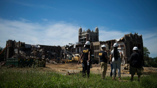 Camden High School alumni gather as demolition continues to the school Thursday, June 14, 2018 in Camden, N.J. Former students came back to witness the unveiling of a 102-year-old time capsule uncovered from when the school was first built in 1916.