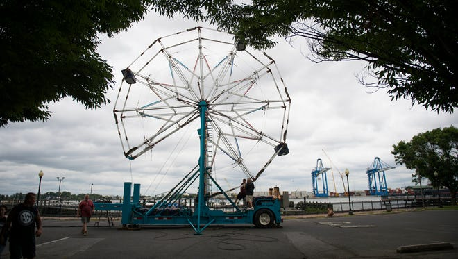 A crew from Lynam's Amusements sets up a Ferris wheel Friday at Proprietors Park in Gloucester City. 'Not Your Mother's Music Fest' will be held Saturday, June 23.