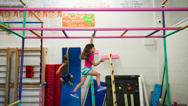 Joseph Yesner, 7, left, and Emma Otto, 5, navigate an obstacle course while participating in a Ninja Warrior program for kids at Will-Moor Gymnastics on July 5 in Mount Laurel.