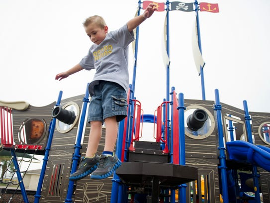 Brady Knight jumps off the 'plank' while playing on the newly installed Jolly Voyager Pirate Ship Playground at the Barber Street Sports Complex in December 2012.