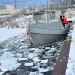 U.S. Coast Guard personnel, in orange at left, watch as Hallack Contracting raises the bow of the fish trap net Sandy on Pere Marquette Lake in Ludington, Mich., Thursday, Feb. 4, 2016. The boat, operated by Levi Stone and licensed by the Little River Band of Ottawa Indians, sunk over the weekend at the breakwall where it has been anchored for months. Thursday was the second day of trying to refloat the boat. This attempt was abandoned. Later, it was raised enough to begin pumping water out of it. (Steve Begnoche/Ludington Daily News via AP) MANDATORY CREDIT