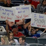 Chicago Cubs fans hold up signs during the ninth inning of a baseball game in 2013 against the Atlanta Braves in Atlanta.