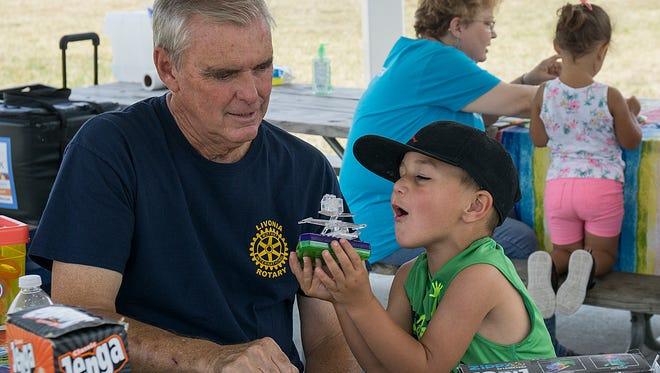 Rotarian Bob Moore and 4-year-old Adam Simon solve engineering problems as they play with Connect 4.