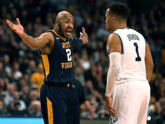 West Virginia's Jevon Carter, left, gestures next to Villanova's Jalen Brunson during the second half of an NCAA men's college basketball tournament regional semifinal Friday, March 23, 2018, in Boston. (AP Photo/Mary Schwalm)