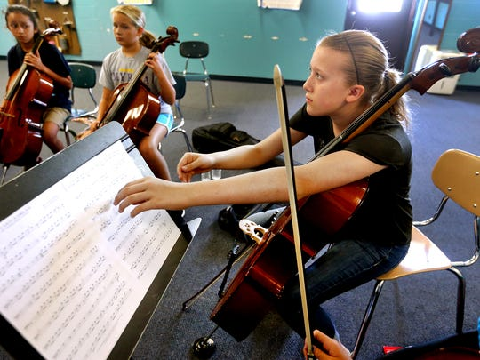 Ashley Albright, 12, changes her music in a cello class during a strings camp at Thurman Francis Arts Academy, on Wednesday July 13, 2016.
