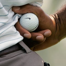 Tiger Woods holds a Nike golf ball while waiting for his turn to putt during second round action in the Bridgestone Invitational Golf Tournament at the Firestone Country Club in Akron, Ohio, in 2007.