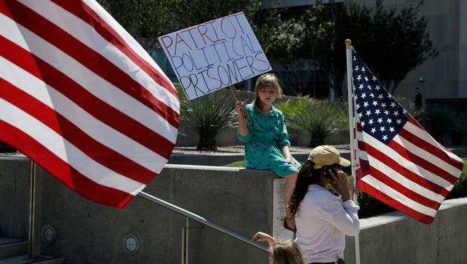 Nine-year-old Paylynn Lawrimore holds up a sign in support of defendants on trial in federal court, Wednesday, April 12, 2017, in Las Vegas.